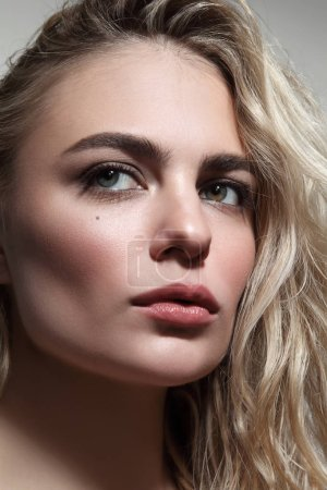 Close-up portrait of young beautiful woman with blond messy hair