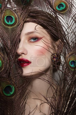 Glamorous portrait of young beautiful woman in peacock feathers