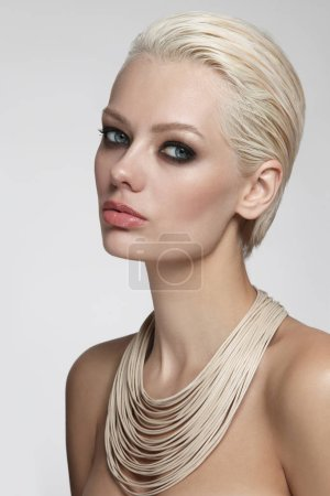 Young beautiful blonde woman with smoky eye make-up and stylish necklace