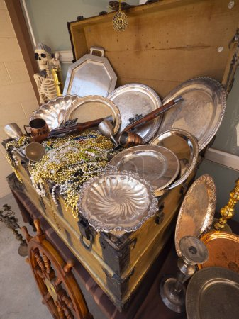 A close up image of pirates chest treasures including, bead necklaces, guns and dinnerware.