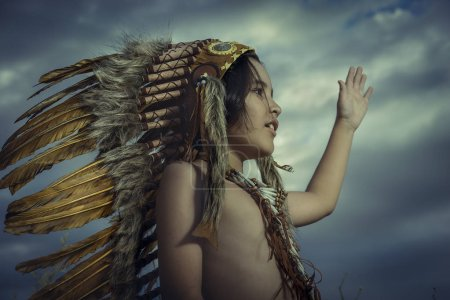 Child dressed as an American Indian at sunset, wears a plume of Indian feathers and breastplate of bones. he has raised his hand as a greeting to nature