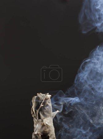 Photo pour Brûlure de cigarette fumée sur fond noir - image libre de droit