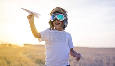 Kid, Little boy wearing helmet and dreams of becoming an aviator while playing a paper plane at sunset