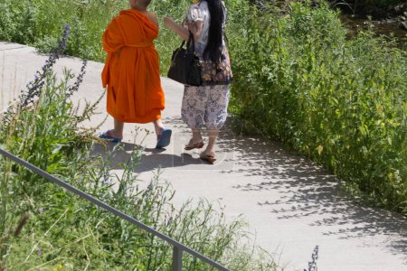on a very sunny day in june in south germany you see single or couple of tibetan monks on a walk in green park