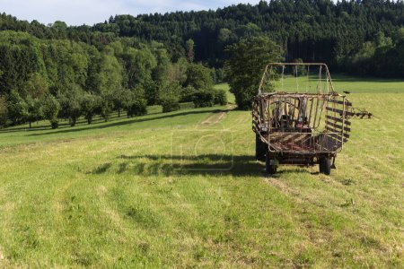 senior farmer haying wiht an old traktor in a summer field in june sunny evening at south germany countryside