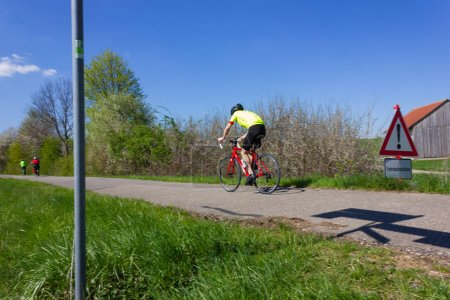 Photo for Cyclists on an road bike on a bikeway at springtime april afternoon with sun and blue sky - Royalty Free Image