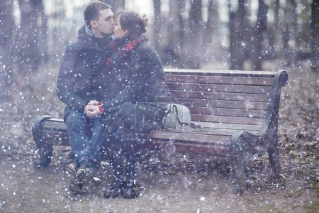 Photo for Young man and woman sitting on bench together in winter park, romantic happy couple - Royalty Free Image
