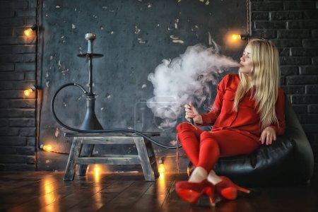 Photo pour Séduisante jeune femme blonde en vêtements rouges, fumer le narguilé - image libre de droit
