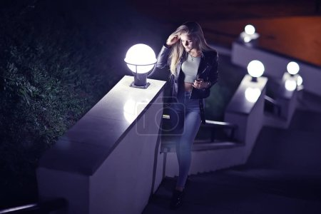 beautiful young woman with long hair posing at the city street at night