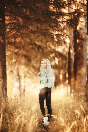 attractive woman running in autumn forest. Young athletic woman jogging outdoor