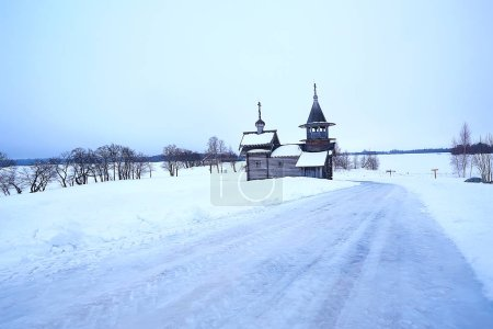 Photo for Lonely wooden church in the field, architecture in the winter landscape - Royalty Free Image