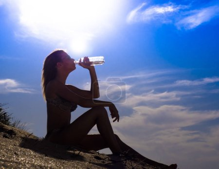 Photo for Beautiful girl with sports forms sports on the beach, drinking water, jumping, running, doing different exercises.silouette of woman sport girl drinking pure water in bottle at sea beach sunset - Royalty Free Image