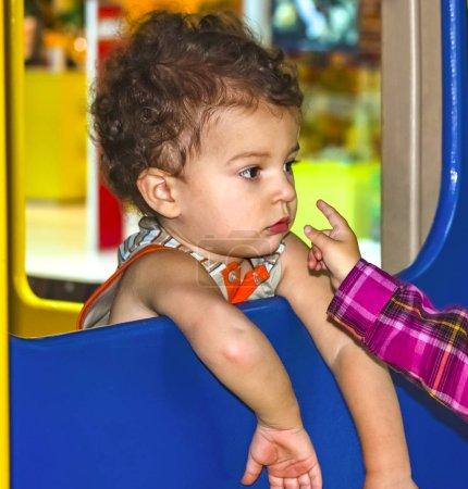 Foto de Adorable pequeño muchacho de niño 1-2 años en el patio, con jersey y pantalones vaqueros de niño - Imagen libre de derechos