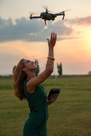 Photo for Young woman landing a drone in her hand while smiling - Royalty Free Image