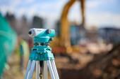 Surveyor equipment theodolite outdoors at construction site - blurry background Surveyor equipment theodolite outdoors and excavator in the background, at construction site