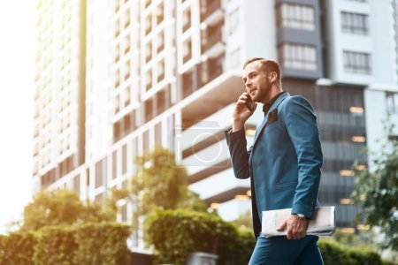 Photo for Rapid tempo of life. Low angle of a self assertive handsome businessman talking on phone and holding a newspaper while walking along the street - Royalty Free Image