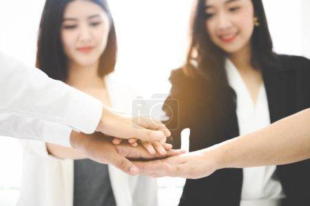 Gros plan belles jeunes femmes d'affaires gens mettre leurs mains ensemble. Une pile de mains. Concept d'unité et de travail d'équipe.