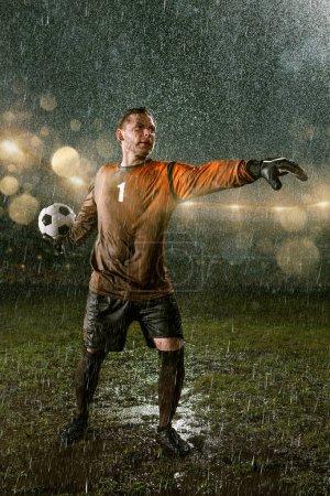 Photo pour Gardien de but de football sur le stade professionnel de pluie de nuit de football. Joueur sale dans des gouttes de pluie avec la bille de football - image libre de droit