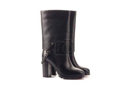 Photo pour Jambes féminines en baskets noires et blanches classiques. Les jambes sont relevées vers le haut et balancent d'un côté à l'autre. Contexte gris. Chaussures classiques. Mode de vie sain - image libre de droit
