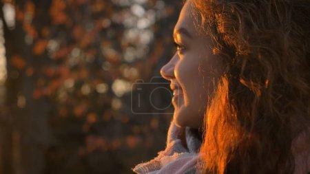 Nahaufnahme Porträt im Profil des lockigen kaukasischen Mädchens, das im herbstlichen Park freudig seitwärts schaut.