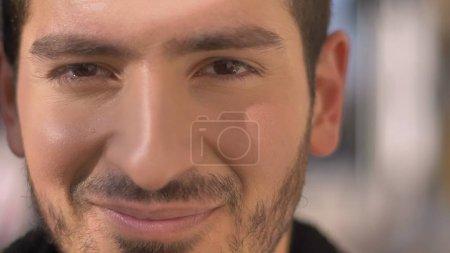 Nahaufnahme Porträt eines kaukasischen Mannes, der vor herbstlichem Straßenhintergrund freudig in die Kamera blickt.