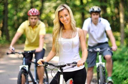 Photo for Portrait of attractive young woman on bicycle and two men behind her - Royalty Free Image
