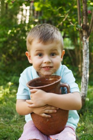 Photo for Cute little boy holding a old clay pot. Milk Jug. Child gardening outdoors. - Royalty Free Image