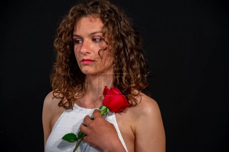 Photo for Closeup of a beautiful brunette girl with curly, sexy hats in a white sleeveless tunic. He is holding a red rose. On a uniform black background, copy space. - Royalty Free Image