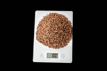 Buckwheat groats on white kitchen scales on a black background, isolate