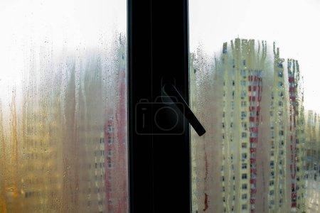 Photo pour Le problème - fenêtres en PVC brume. En dehors de la fenêtre brouillé l'image des maisons - image libre de droit