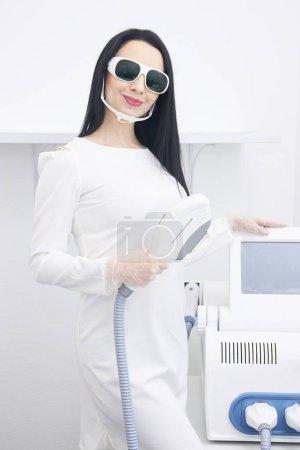 Girl cosmetician. Modern equipment. White robe. Light background.