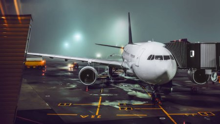 view of aircraft in illuminated foggy airport at night