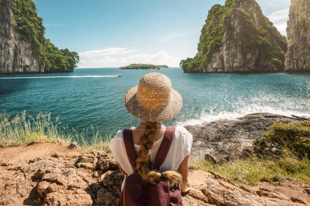 Photo for Girl traveler wearing straw hat in rocky marine landscape - Royalty Free Image
