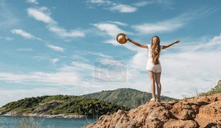 Photo pour Fille voyageur tenant chapeau de paille dans un paysage marin rocheux - image libre de droit