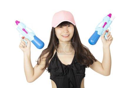 Sexy femme Chinoise Américaine portant un maillot de bain une pièce noir et jouant avec des pistolets à eau bleue isolés sur un fond blanc