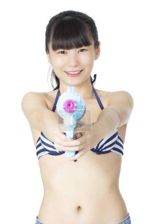 Sexy femme Chinoise Américaine portant un maillot de bain bikini et jouant avec des pistolets à eau bleue isolés sur un fond blanc