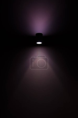 Single spotlight with a purple light beam