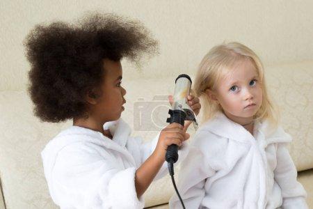 Photo pour Les jeunes enfants jouent avec les fers à friser. Les filles en manteaux blancs, Caucasiens et Afro-américains jouent et considèrent les bigoudis électriques . - image libre de droit