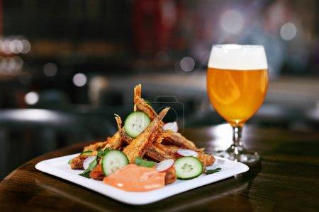 Photo pour Nourriture et boisson. Poisson frit et bière sur la table dans le restaurant de bière. Haute résolution . - image libre de droit