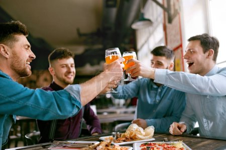 Men Drinking Beer In Pub. Friends Toasting With Alcohol Drinks in Bar. High Resolution.
