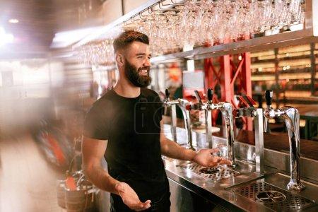 Photo pour Bar Pub. Homme Barman debout au comptoir de bar près des robinets de bière. Haute résolution . - image libre de droit