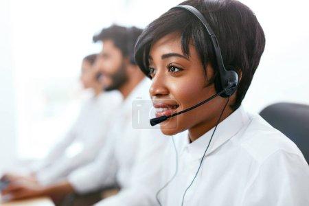 Photo pour Contact Center Operator Consulting Client On Hotline. Une femme afro-américaine attirante au service des clients du Call-Center. Haute résolution - image libre de droit