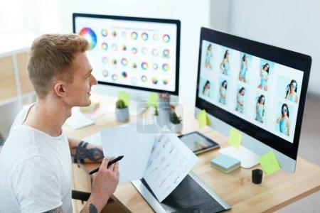 Foto de Diseñador Web trabajando en proyecto de diseño en la oficina. Hombre Webdesign creando en equipo. Alta resolución - Imagen libre de derechos