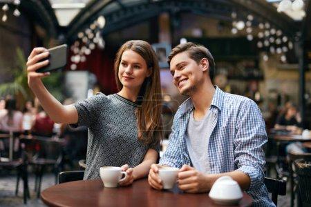 Photo pour Couple faisant des photos sur téléphone portable dans Café. Femme et homme ayant rendez-vous dans un café. Haute résolution - image libre de droit