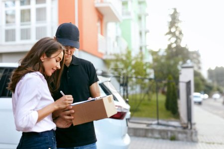 Photo for Delivery Courier. Man Delivering Package To Woman. Client Signing Delivery Documents. High Resolution - Royalty Free Image