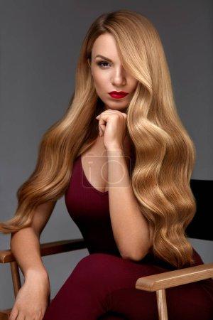Photo pour Coiffure. Belle femme aux cheveux blonds longs ondulés en bonne santé. Portrait de fille avec maquillage de beauté et coiffure bouclée. Haute résolution - image libre de droit