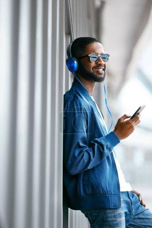 Photo pour Homme écoutant de la musique dans les écouteurs sur le téléphone dans la rue. Beau mâle noir dans les vêtements de mode. Haute résolution - image libre de droit