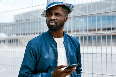 Photo pour Bel homme noir dans les vêtements de mode avec téléphone sur la rue. Portrait d'homme africain élégant avec téléphone en ville. Haute résolution - image libre de droit