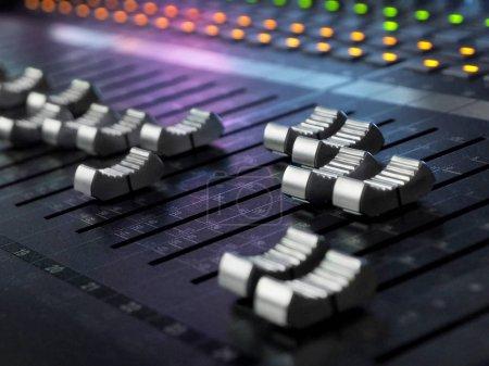 Photo pour Studio d'enregistrement sonore Mixage Bureau Gros plan. Panneau de contrôle de mélangeur de musique avec des lumières colorées. Haute résolution - image libre de droit