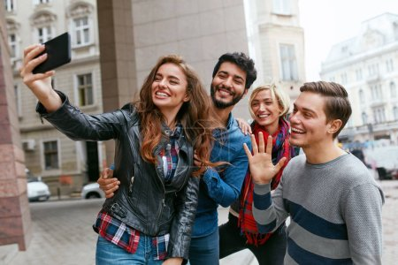 Photo for People Using Phone Taking Photos On Street, Video Calling. Happy Friends Having Fun Outdoors. High Resolution - Royalty Free Image